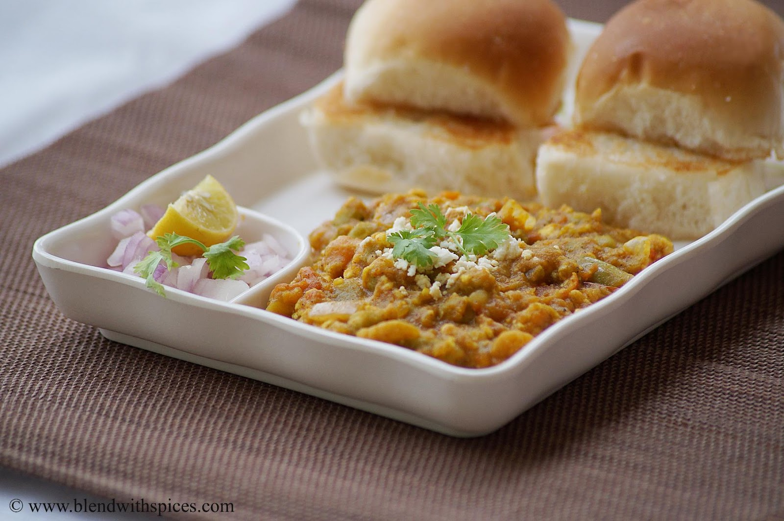the best pav bhaji served with buttered pavs and onion lemon wedges